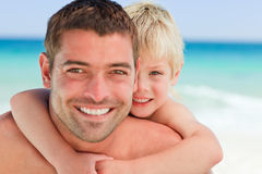 Smiling father having son a piggyback. At the beach Stock Images