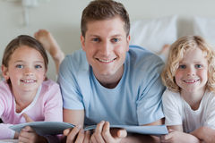 Smiling father with his children and a magazine Stock Photography