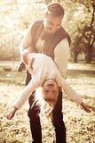 Smiling father and his daughter playing together. In autumn day and enjoying in park stock images