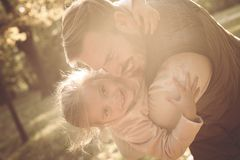 Smiling father and his little girl plying in park together. royalty free stock images