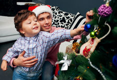Smiling father and his son on Christmas. Smiling father and his son opening Christmas presents in the living-room royalty free stock photo