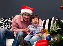 Smiling father and his son on Christmas. Smiling father and his son opening Christmas presents in the living-room royalty free stock image