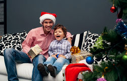 Smiling father and his son on Christmas. Smiling father and his son opening Christmas presents in the living-room royalty free stock images