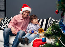 Smiling father and his son on Christmas. Smiling father and his son opening Christmas presents in the living-room stock photo