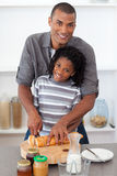 Smiling father and his son cutting bread Royalty Free Stock Images