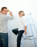 Smiling father and his son decorating a room Royalty Free Stock Images