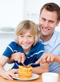 Smiling father and his son eating waffles Royalty Free Stock Photography