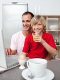 Smiling father and his son having breakfast Stock Images