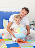 Smiling father and his son looking at a globe. Smiling father and his son looking at a terrestrial globe sitting on a bed stock image