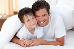 Smiling father and his son lying on bed Stock Photo