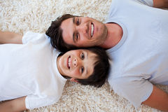 Smiling Father and his son lying on the floor Stock Images