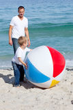 Smiling father and his son playing with a ball. At the beach Stock Images