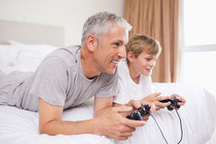 Smiling father and his son playing video games Stock Image