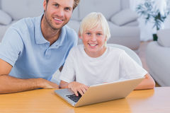 Smiling father and his son using laptop Stock Photo