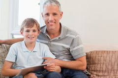 Smiling father and his son using a tablet computer. In a living room Royalty Free Stock Image
