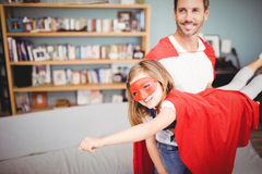 Smiling father holding daughter wearing superhero costume Stock Images