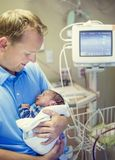Smiling father holding his newborn baby son in a hospital room Royalty Free Stock Images