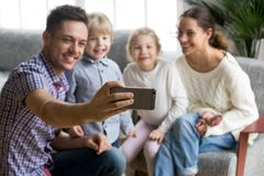 Smiling father holding smartphone taking selfie of happy family royalty free stock photos