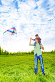 Smiling father holds kid and watches kite in air Stock Images