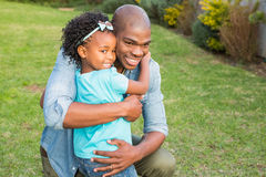 Smiling father hugging his daughter. In the garden stock image