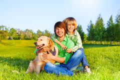 Smiling father, kid  and dog sit in park on grass Royalty Free Stock Photos