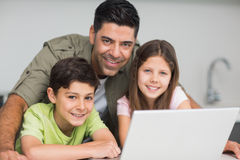 Smiling father with kids using laptop in kitchen Royalty Free Stock Image
