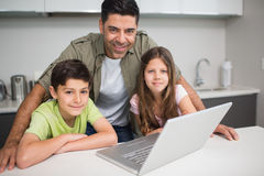 Smiling father with kids using laptop in kitchen Royalty Free Stock Photography