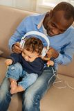 Smiling father listening to music with his baby stock photo