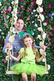 Smiling father and little girl with shamrock on head on swing Royalty Free Stock Photography