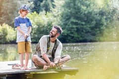 Smiling father looking at son standing on pier while fishing in lake royalty free stock photo