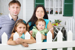 Smiling father, mother, baby and daughter stand next to fence Royalty Free Stock Photo