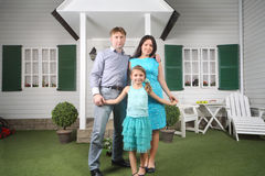 Smiling father, mother and daughter stand near porch Stock Image