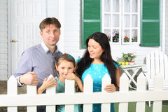 Smiling father, mother and little daughter stand next to fence Stock Images