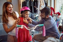 Smiling father and mother shopping new bicycle and helmets for little girl in bike shop. Smiling father and mother shopping new bicycle and helmets for happy stock image