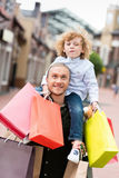 Smiling father piggybacking his little son with shopping bags at street Royalty Free Stock Photo