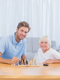 Smiling father playing chess with his son. In the living room stock photography