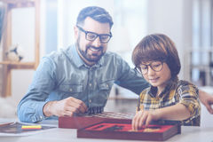 Smiling father playing chess with son. Like father, like son. Father and son both wearing glasses whilst playing chess and smiling at home stock images