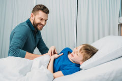 Smiling father playing with sick little boy lying in hospital bed. Dad and son in hospital Stock Photo