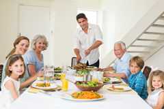 Smiling father serving meal to family. Portrait of smiling father serving meal to family at dining table Royalty Free Stock Image