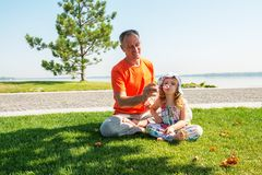 Smiling father with a small daughter blow bubbles and having fun. Smiling father with a small daughter relax on a green meadow near the river on a beautiful Royalty Free Stock Photography