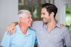 Smiling father and son with arm around royalty free stock photography