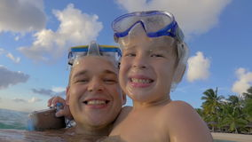 Smiling father and son bathing in the sea stock video footage