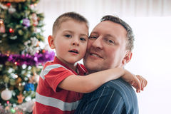 Smiling father and son at christmas. Portrait of a smiling father hugging his young son while standing in front of a Christmas tree during the holidays Stock Images