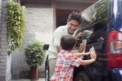 Smiling Father and Son Clean their Minivan Together Stock Images