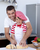 Smiling father and son cutting bread Royalty Free Stock Photography