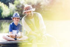 Smiling father and son fishing in lake while sitting on pier stock photos