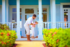Smiling father and son having fun in front of the house. Smiling family, father and son having fun in front of the house royalty free stock images