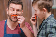 Smiling father and son having fun with pepper moustaches Royalty Free Stock Photos