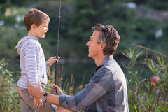 Smiling father and son holding fishing rod. By plants royalty free stock images