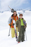 Smiling father and son holding skis and poles on mountain Stock Image